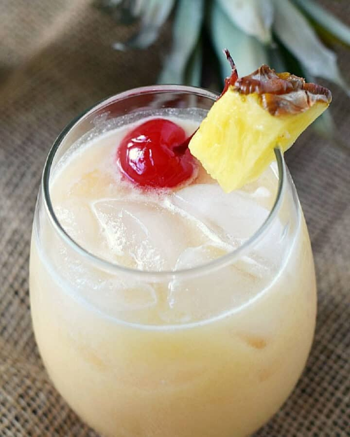 A creamy cocktail in an ice filled glass garnished with a pineapple wedge and cherry.
