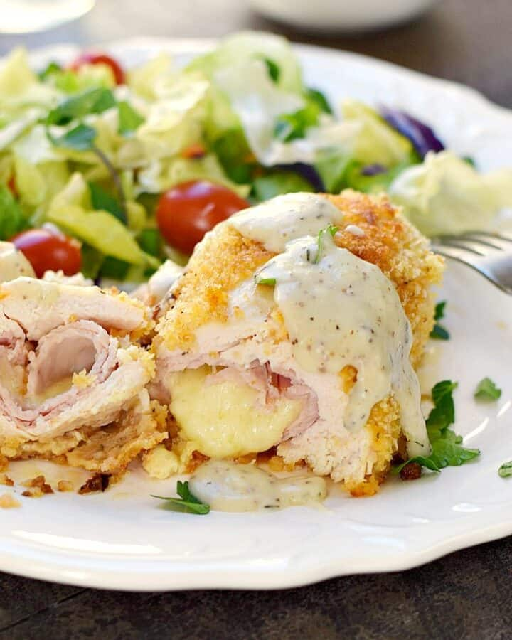 panko crusted chicken rolled around ham and cheese, but in half and sitting on a white plate with a tossed salad