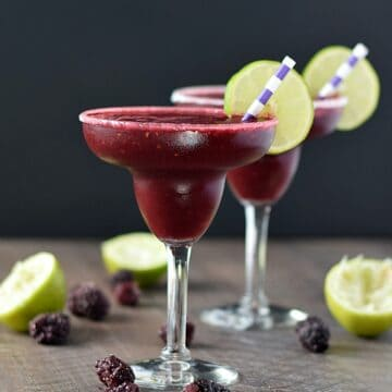two Frozen Blackberry Margaritas in margarita glasses garnished with lime wheels and striped straws