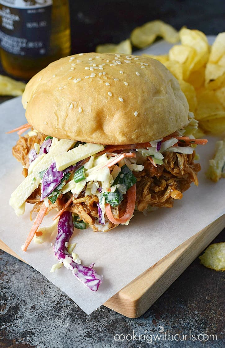 Slow Cooker Barbecue Chicken Sandwiches topped with Apple Coleslaw sitting on a parchment paper lined cutting board with chips and a bottle of Corona in the background