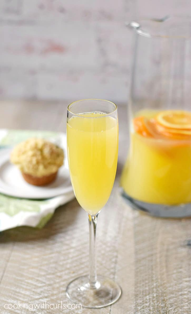 a champagne flute filled with a classic mimosa with a blueberry muffin on a white plate and a half-full pitcher of mimosas in the background