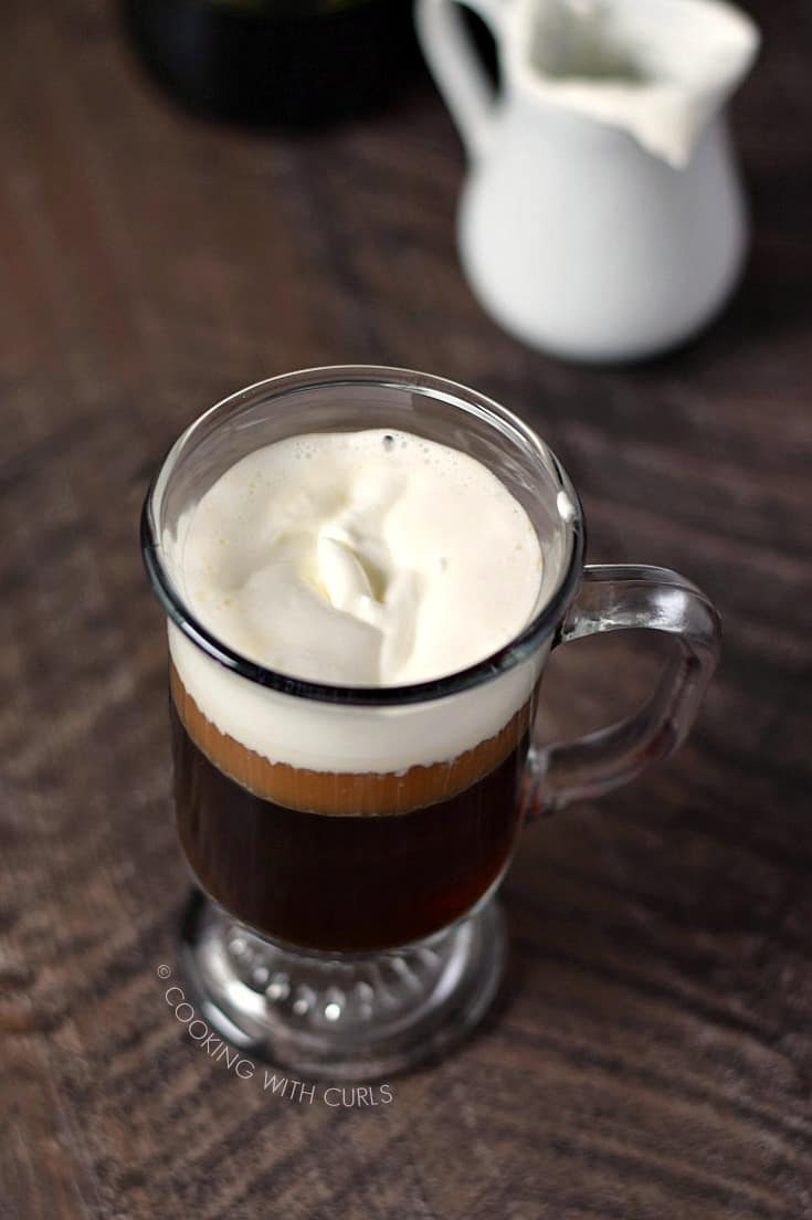Looking down on an Irish Coffee in a traditional glass mug with a creamer pitcher in the upper right corner
