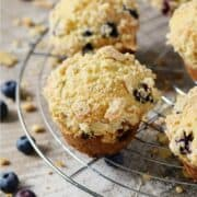 Streusel topped blueberry muffins on a wire cooling rack and title graphic across top.