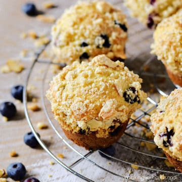 Streusel topped blueberry muffins on a wire cooling rack.