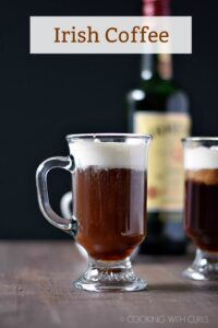 Two glass mugs filled with Irish Coffee sitting in front of a bottle of Jameson whiskey