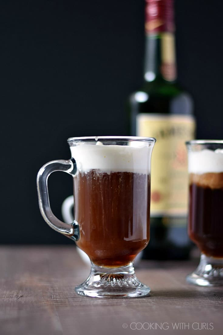 side view of two Irish Coffees with a bottle of Jameson in the background