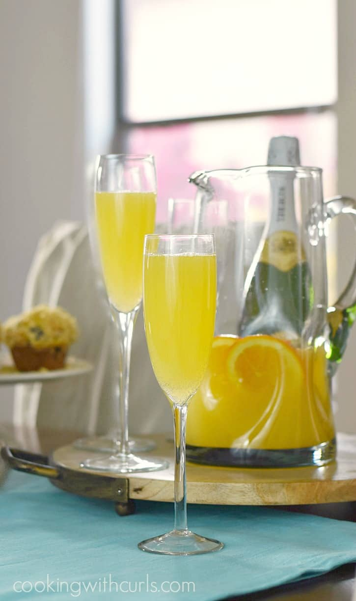 two champagne flutes filled with mimosas sitting on a round, wooden serving board with an open bottle of champagne and a blueberry muffin in the background in front of a bright window