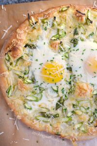 pizza topped with asparagus, cheese and sunny side up eggs on a brown sheet of parchment paper