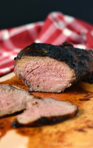 slices of tri-tip laying on a wood cutting board with a red and white check napkin in the background