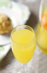 champagne flute filled with a classic mimosa with a blueberry muffin and a pitcher of mimosas in the background