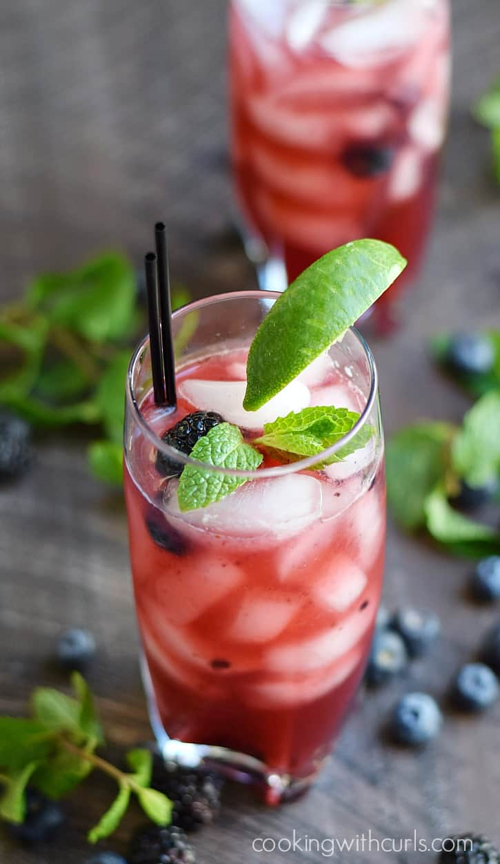 Two tall glasses filled with smashed berries, fresh berries, ice and mint leaves surrounded by blueberries and mint leaves.