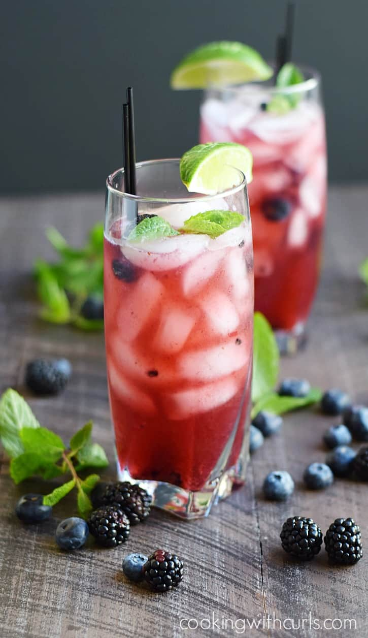 Two tall glasses filled with smashed berries, fresh berries, ice and mint leaves surrounded by blueberries, blackberries, and mint leaves.