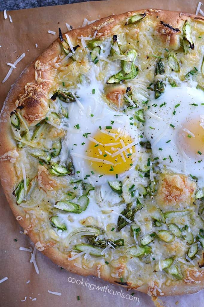 Pizza topped with shaved asparagus, grated parmesan and soft cooked eggs.