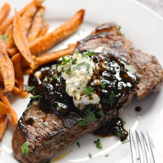 Pub-Style Steak with caramelized shallots and roasted garlic, goat cheese, and chives butter on a white plate with sweet potato fries on the side