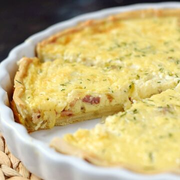sliced quiche in a ceramic white tart pan