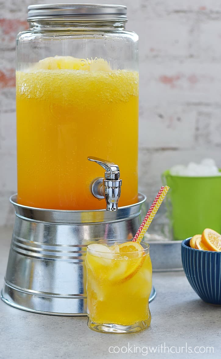 A glass of this delicious Orange Peach Mango Spritzer is the perfect way to cool off on a hot summer day | cookingwithcurls.com