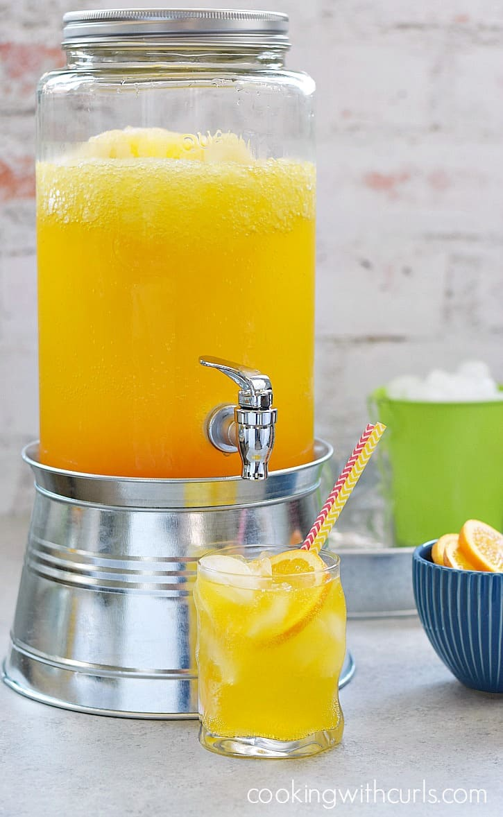 a large glass dispenser filled with orange peach mango spritzer with a full glass of spritzer, a green bucket of ice and a blue bowl full of orange slices