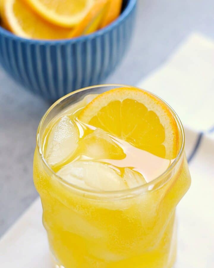a glass of orange peach mango spritzer sitting on a blue striped napkin with a blue bowl of orange slices on the left side