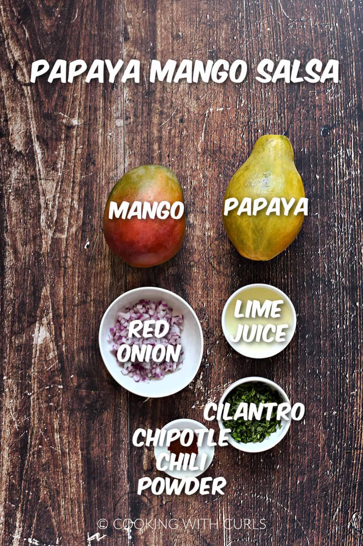 A mango, papaya, chopped red onions, lime juice, chopped cilantro, and chipotle chili powder to make papaya mango salsa.