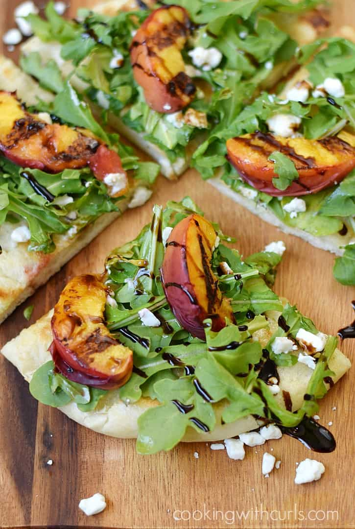 Celebrate summer goodness with a Grilled Peach and Arugula Pizza topped with goat cheese and drizzled with balsamic glaze | cookingwithcurls.com