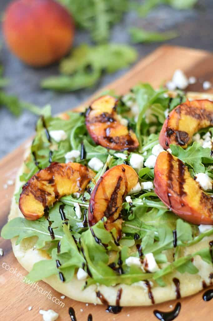 Grilled Peach and Arugula Pizza topped with goat cheese and drizzled with balsamic glaze | cookingwithcurls.com