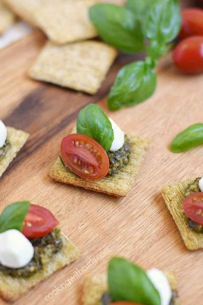 TomatoPestoCheesecuit {aka Caprese Bites} lined up on a wooden serving board.
