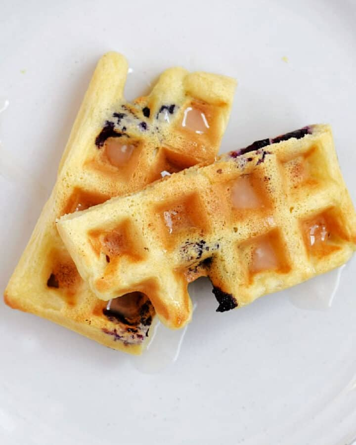 A blueberry and lemon waffle that is cut in half drizzled and with glaze on a white plate.