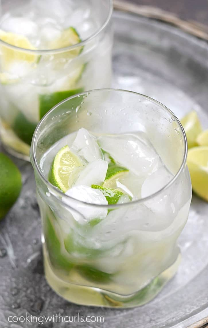 two glasses of ice and limes on a silver tray filled halfway with a caipirinha