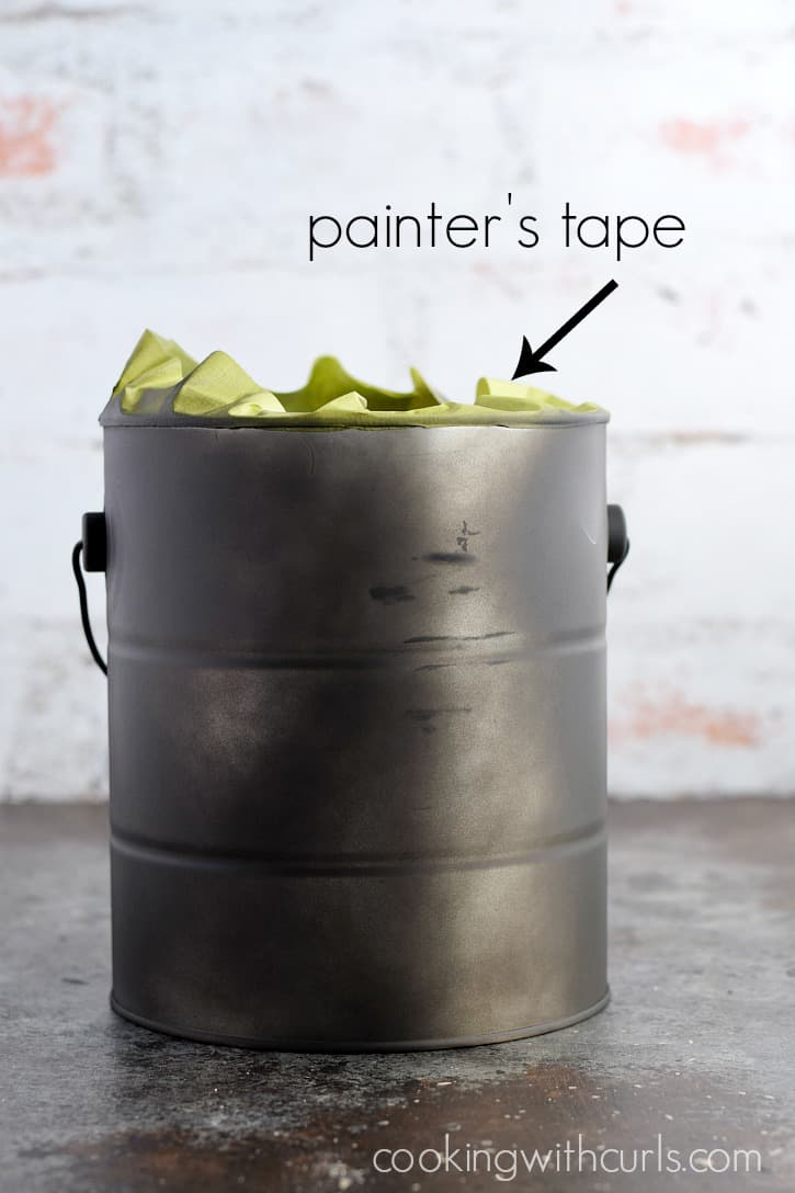 A metal paint container spray painted black with green painters tape around the top edge.