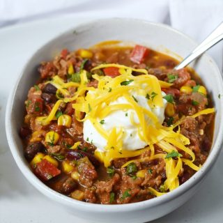 A bowl of Southwest Chili with Black Beans and Corn topped with sour cream and shredded cheddar cheese
