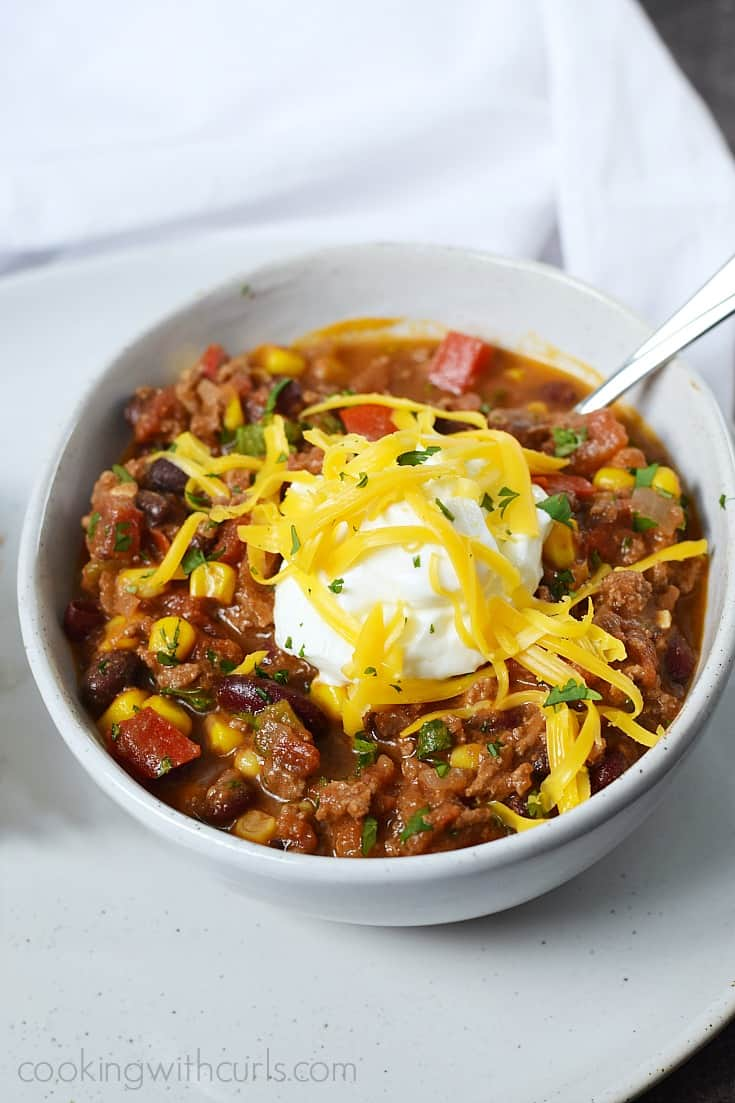 Southwest Chili with Black Beans and Corn topped with sour cream and shredded cheddar cheese in a white bowl.