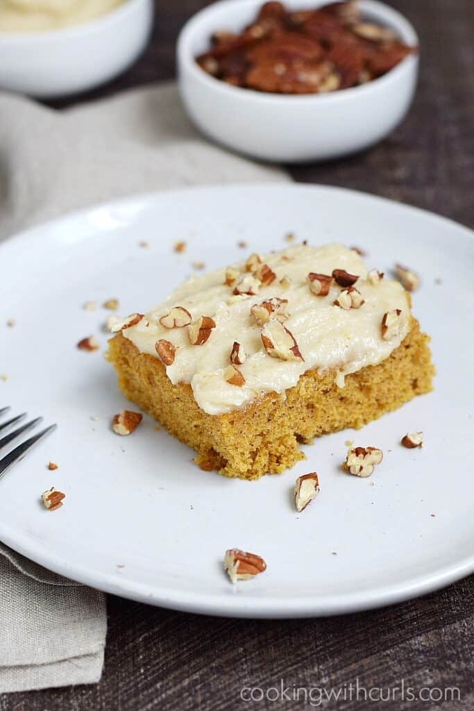 ! Pumpkin Spice Bar on a white plate with pecans and additional frosting in the background in small white bowls