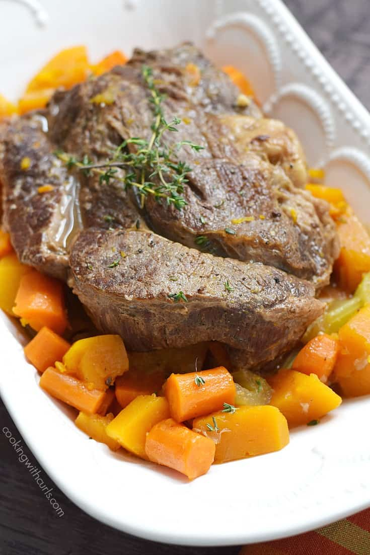 pot roast surrounded by carrots and squash in a white bowl