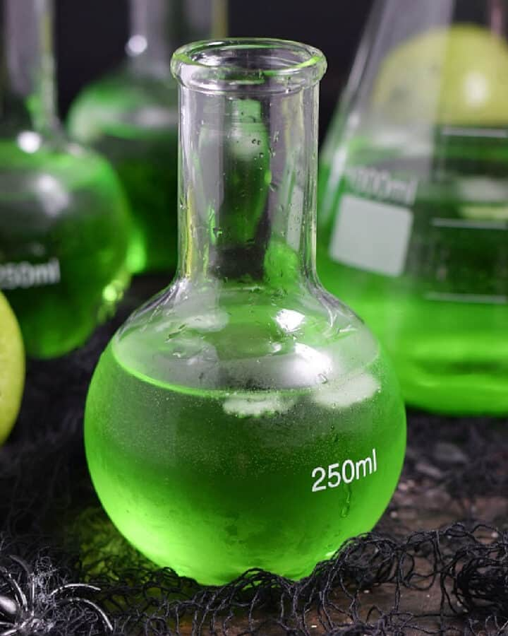 Three Poisoned Apple Cocktails in glass science bottles, two green apples, and a large beaker.