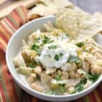 a bowl of white chicken chili topped with sour cream and green onions with tortilla chips stacked on the side