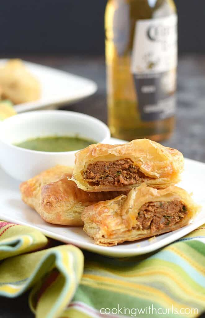 Puff Pastry Chorizo Rolls stacked on a white plate with creamy cilantro sauce on the plate and a bottle of corona in the background
