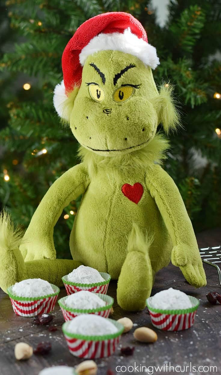 Five snowball cookies in red and white striped paper liners sitting in front of a Grinch doll with a lit tree behind it.