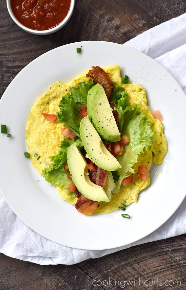 """Three slices of avocado, two slices of bacon, lettuce leaves and chopped tomato laying on a flat egg """"tortilla""""."""