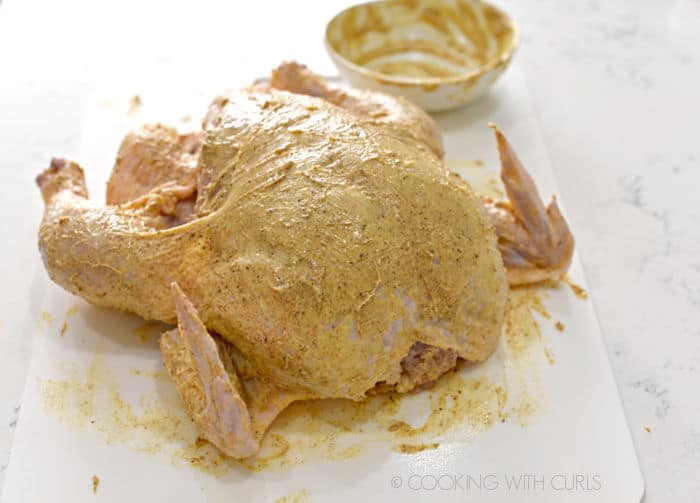 A whole chicken on a white cutting mat rubbed with seasoned butter.