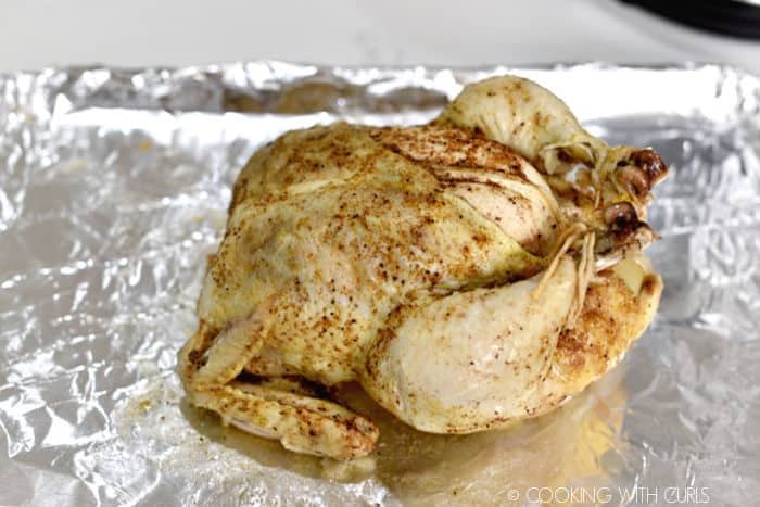 Cooked whole chicken on a foil lined baking sheet.