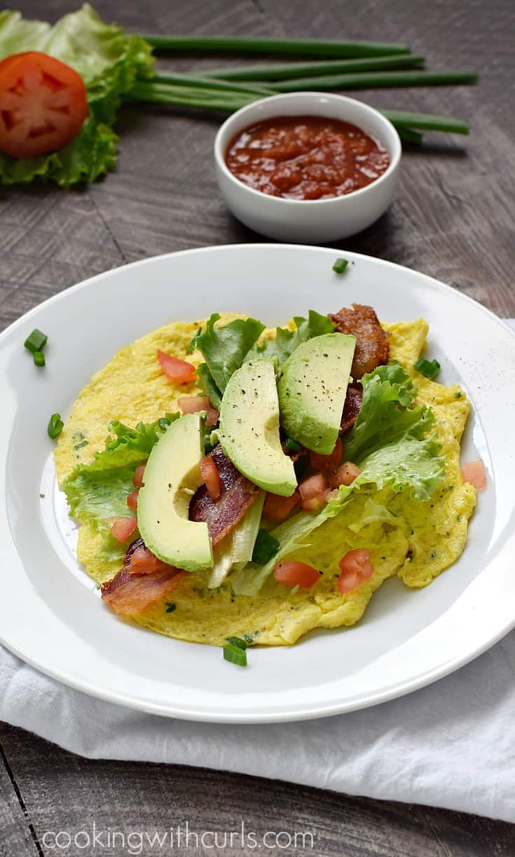 """Avocado slices, bacon, chopped tomatoes, and lettuce leaves on top of a scrambled egg """"tortilla"""" on a small plate."""