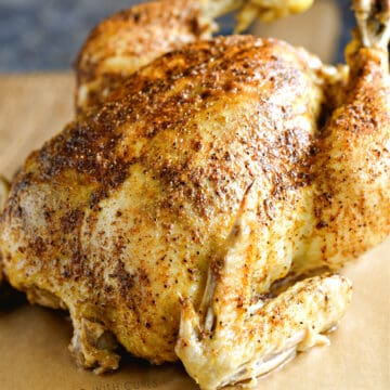 a close-up image of a cooked whole chicken on a wooden cutting board.