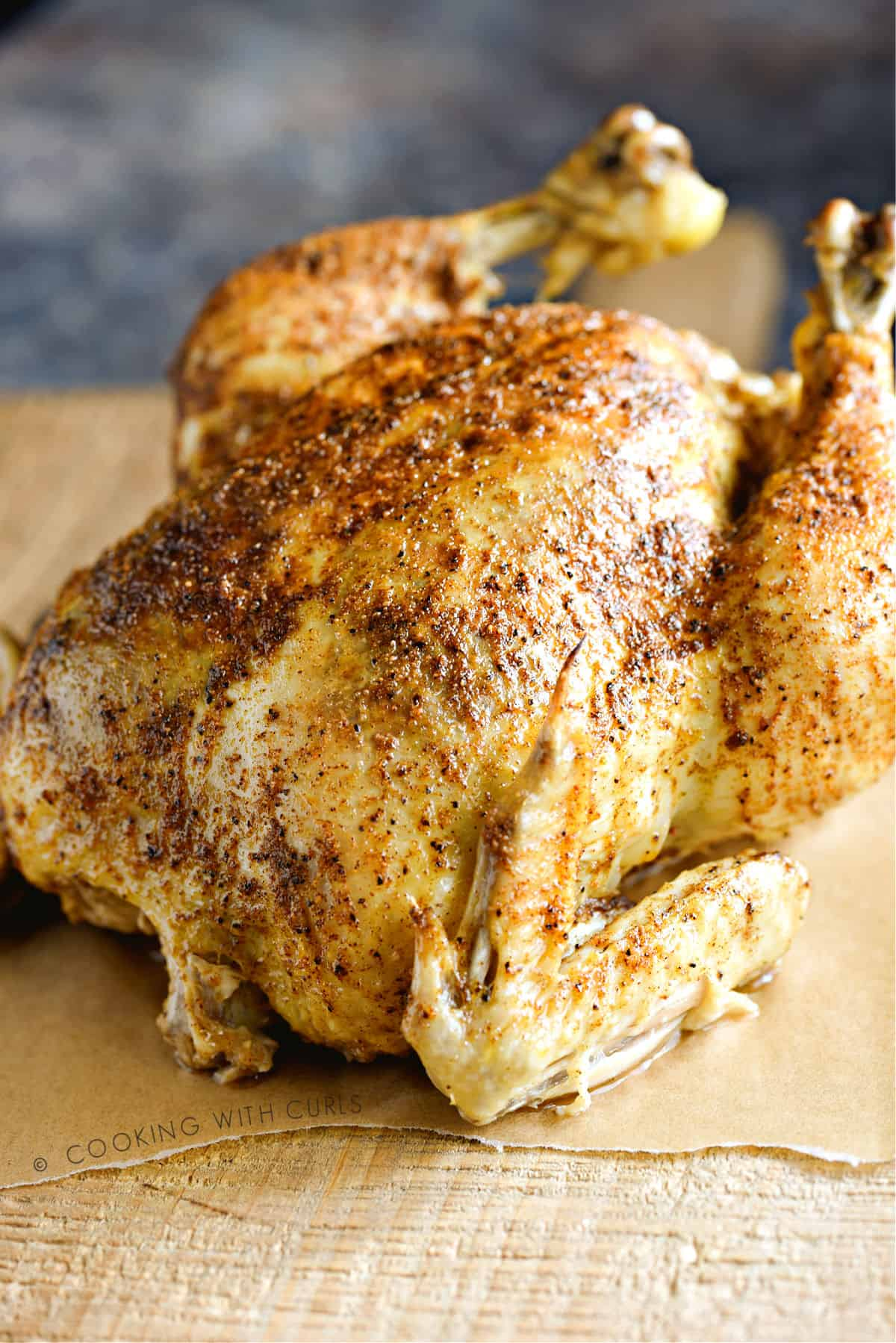 a whole chicken that was cooked in a pressure cooker sitting on a wooden cutting board.