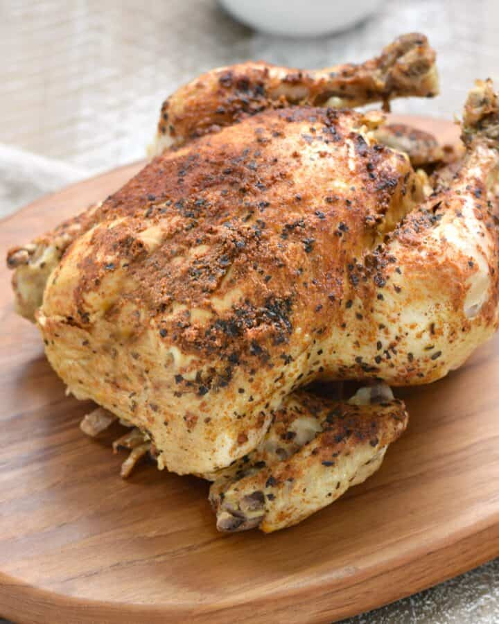 instant pot whole chicken faux-tisserie style sitting on a wooden cutting board.
