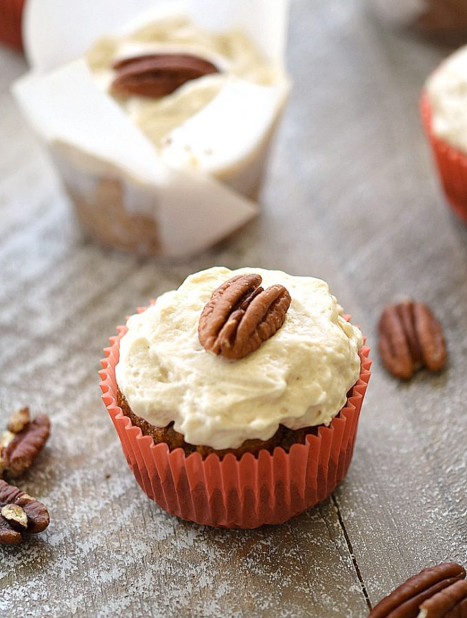 Paleo Maple Carrot Cupcakes in orange or white wrappers on a wooden board with pecans scattered around