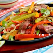 Strips of charred steak, bell peppers and onions in a fajita skillet.