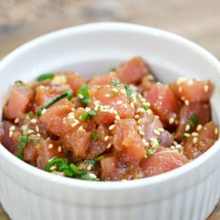 raw ahi poke sprinkled with sesame seeds in a white bowl