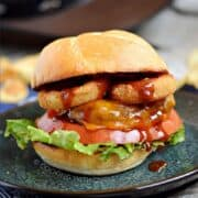 A cheeseburger topped with lettuce, tomato, onion rings, barbecue sauce and a toasted bun with title graphic across the top.