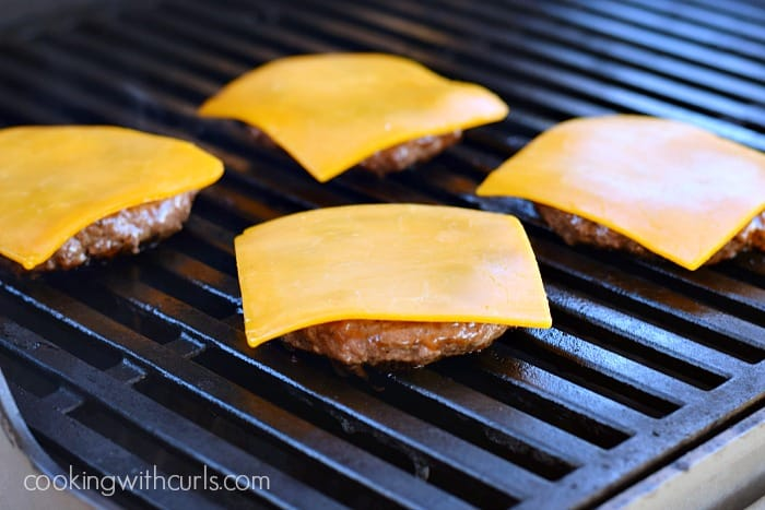 Four burger patties on the grill topped with a slice of cheddar cheese.