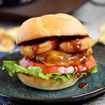 A cheeseburger topped with lettuce, tomato, onion rings, barbecue sauce and a toasted bun.
